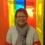 Picture of Head Teacher in front of rainbow curtains